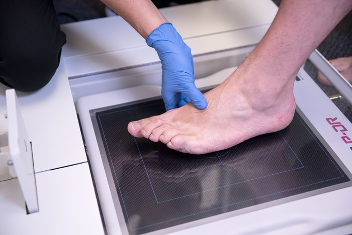 hand placing a foot on scanner