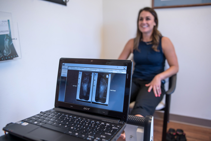 foot xray on laptop screen in front with patient in back